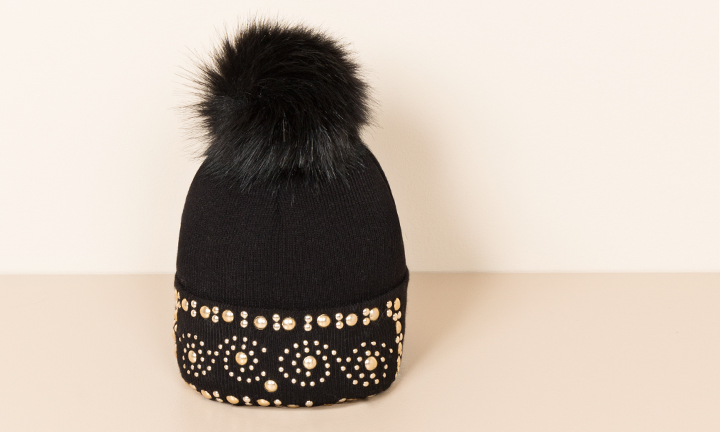 Soft warm black beanie with gold studded detailing and a large soft faux fur pom-pom on top.